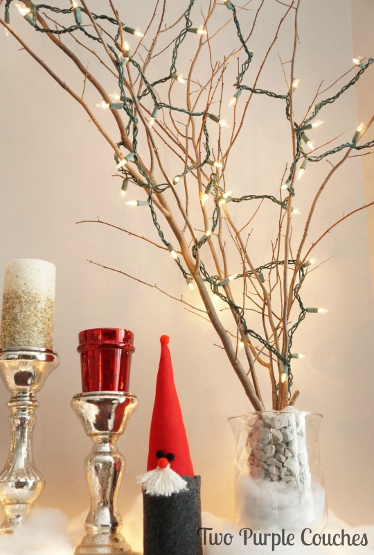 Lit Branches add warmth to a beautiful holiday mantel. via www.twopurplecouches.com