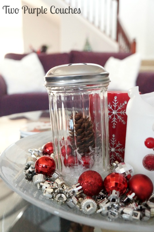 Pretty glass jar snow scenes make a great centerpiece paired with candles, ornaments and ornament caps! via www.twopurplecouches.com