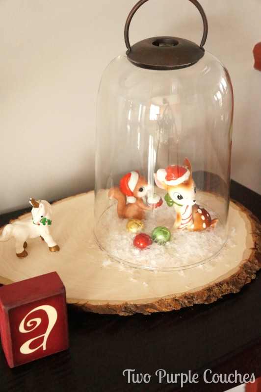Cute vintage ornaments and decor displayed on a wood slice cloche. via www.twopurplecouches.com