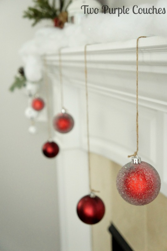 Love this easy decorating idea - hang ornaments from the mantel for an extra pop of color and shimmer!