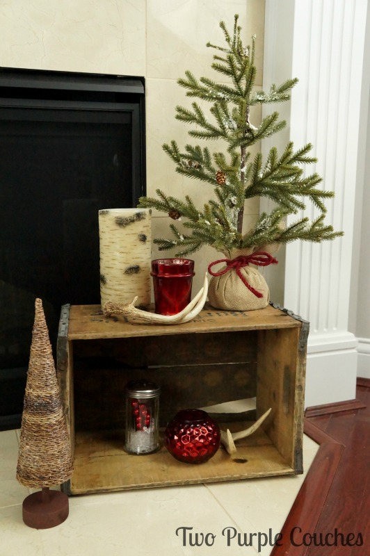 Repurpose a weathered beer crate to display trees, candles, and antlers for rustic Christmas decor.