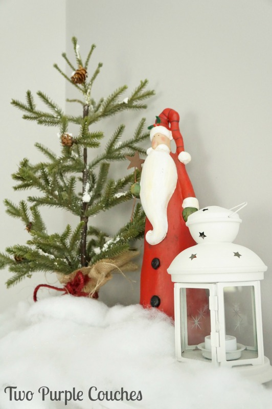 Pair a rustic Santa with a faux tree and lantern for a pretty holiday vignette.