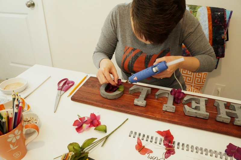 gluing-flowers-to-sign