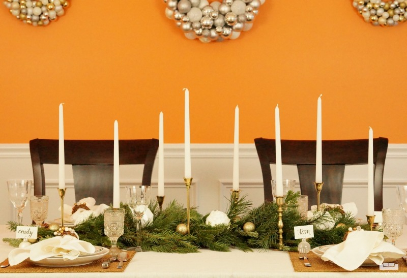 Beautiful holiday table idea! Use fresh, natural greenery and gold or brass candlesticks to create this simple yet elegant DIY evergreen Christmas tablescape.
