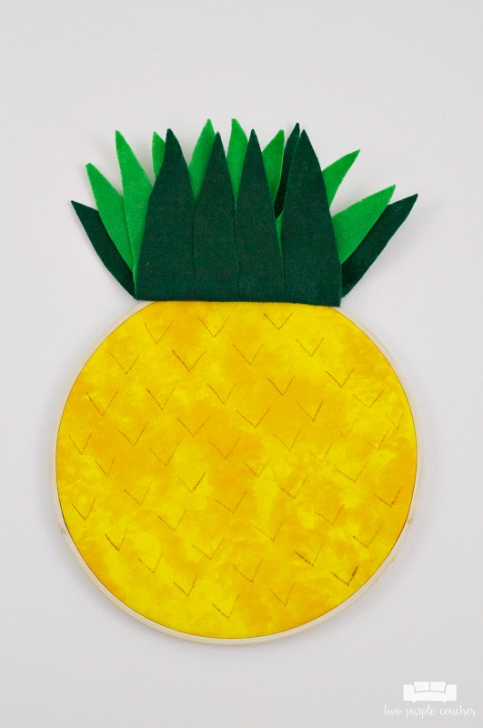 Learn how easy it is to make your own pineapple embroidery hoop art! Transform a simple hoop into trendy pineapple art for your home using fabric & felt!