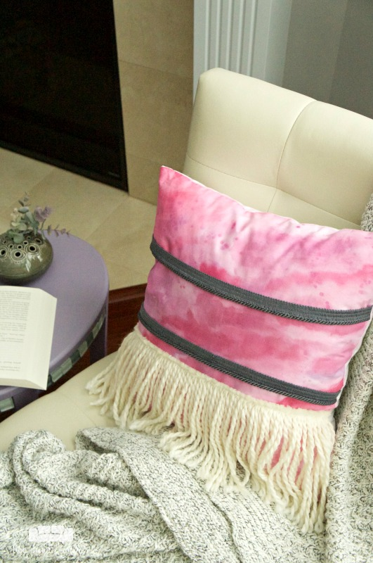Add a splash of bohemian style to your home or dorm with this easy painted boho pillow with yarn fringe.