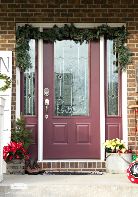 Create a festive holiday porch with these simple decorating ideas! All you need is some Garland, ornaments, evergreen and an easy DIY sign!