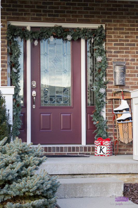 Simple Christmas front porch decorations a vintage touch. Create a pretty holiday porch with garland, lights and a vintage sled draped with ice skates!