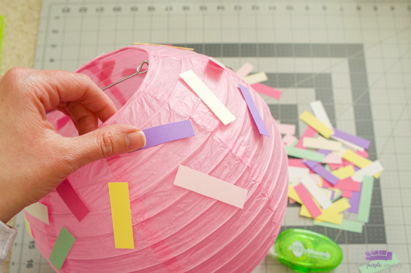 attaching sprinkles to paper lantern